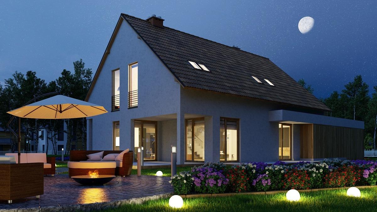 Einfamilienhaus mit Licht im Garten nachts durch Leuchtkugel und Feuerschale