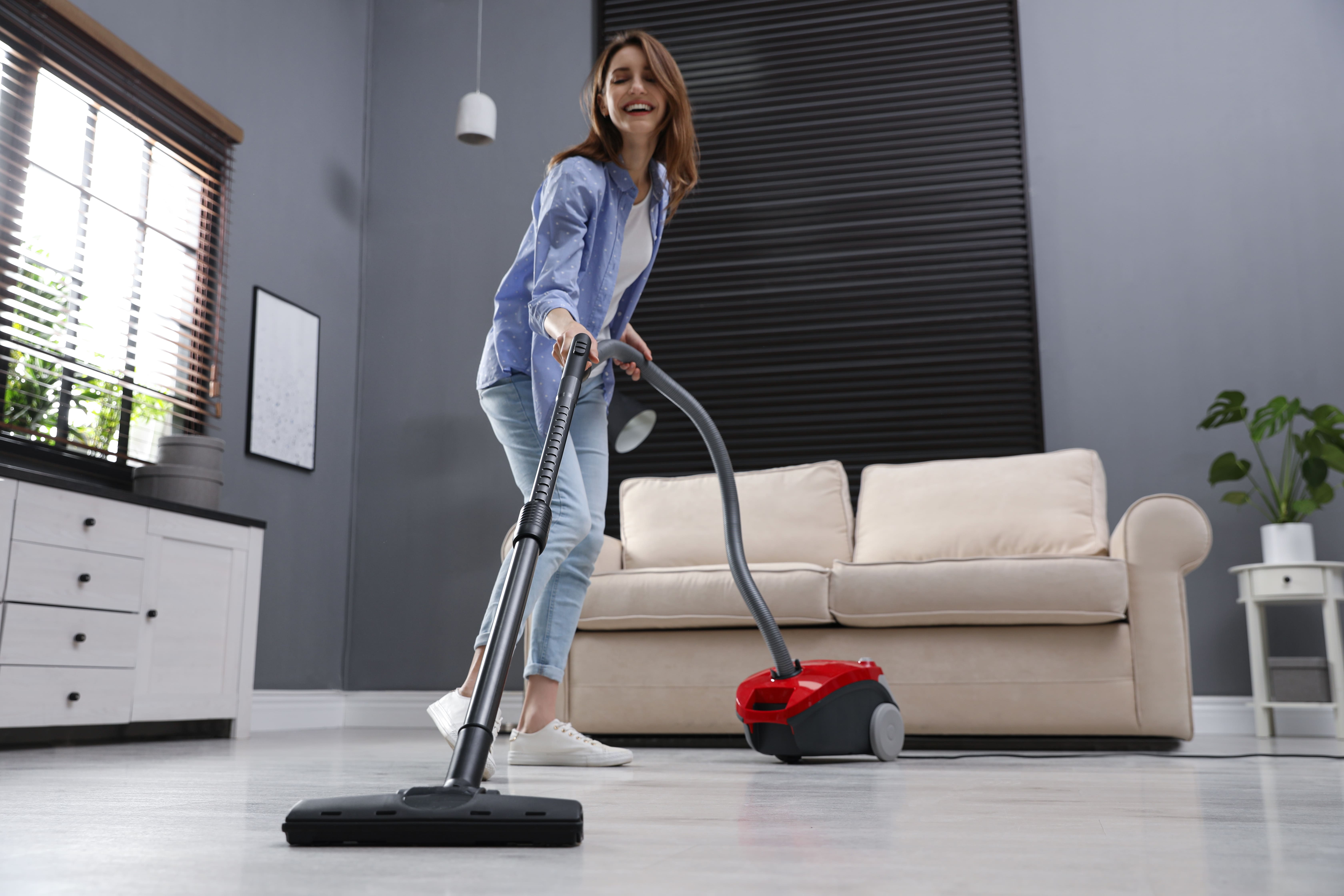 Odkurzacze workowe – kobieta odkurzająca dom